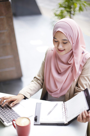 Smiling young Malay woman using laptop