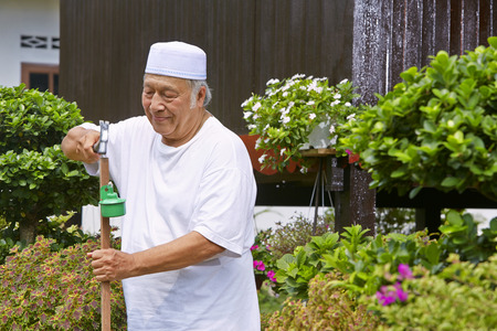 Senior man setting up pelita torches around the house LANG_EVOIMAGES