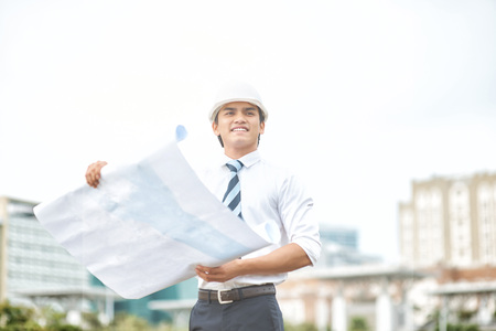 executive helmet: Young businessman wearing safety hat and reviewing blueprints on site LANG_EVOIMAGES