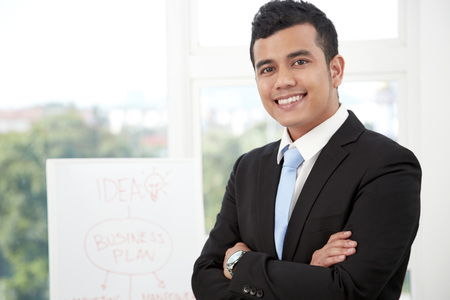 business: Happy businessman standing with arms crossed in front of flipchart in conference room