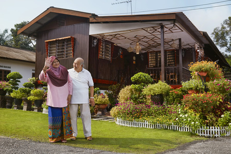 Senior couple smiling and waving in front of wooden house