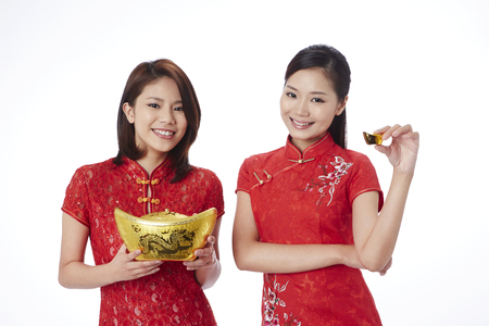 lucky charm: Young women in traditional Cheongsam holding gold ingot LANG_EVOIMAGES