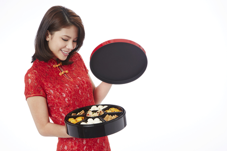 titbits: Young woman in traditional Cheongsam holding an assorted tasty treats box