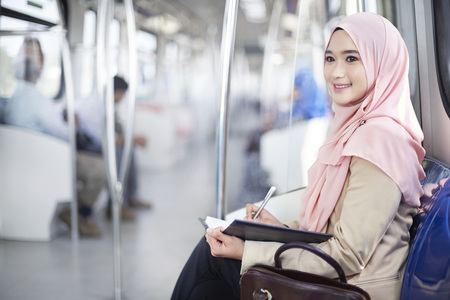 Young Malay woman writing notes in a train LANG_EVOIMAGES