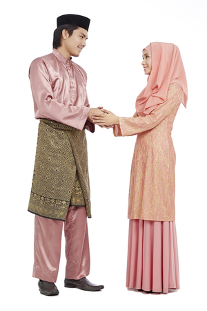 Couple in traditional Malay clothes greeting each other with the Salam greeting gesture