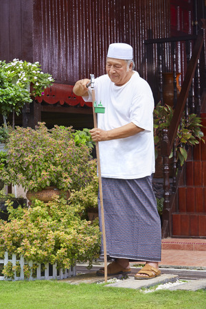 Senior man setting up pelita torches around the house LANG_EVOIMAGES
