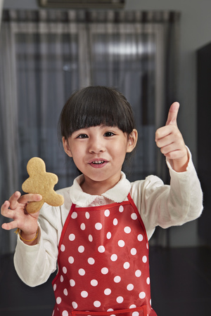 gingerbread man: A smiling girl posing with a freshly baked cookies