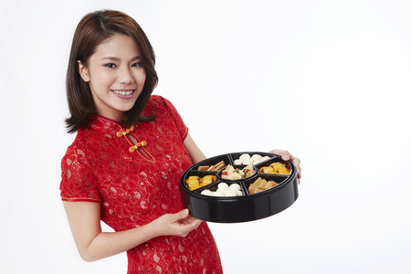 toothy: Young woman in traditional Cheongsam holding an assorted tasty treats box