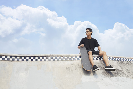 Young man looking away while holding a skateboard at a skate park