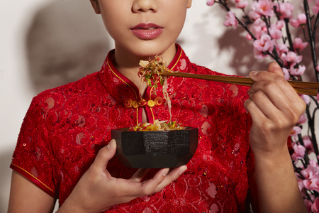 Young woman in Cheongsam, holding a bowl of Yee Sang and chopsticks