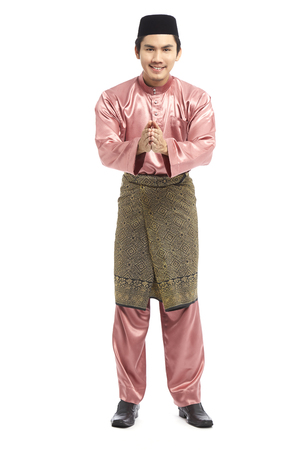 Man in traditional Baju Melayu with hands in Salam greeting gesture