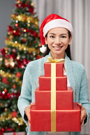 blessings: Woman in Santa Claus hat holding gift