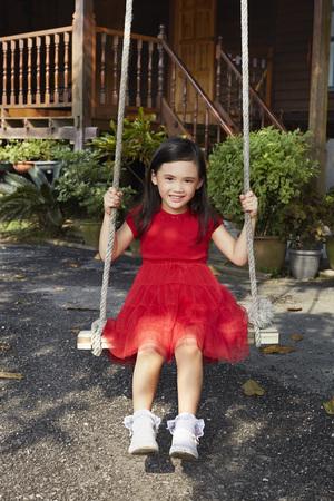 vestidos de epoca: Cheerful little girl playing on a swing