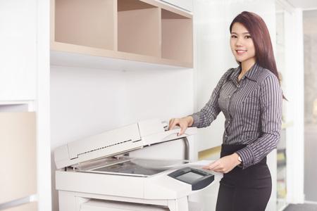 photocopy: Young businesswoman using photocopy machine