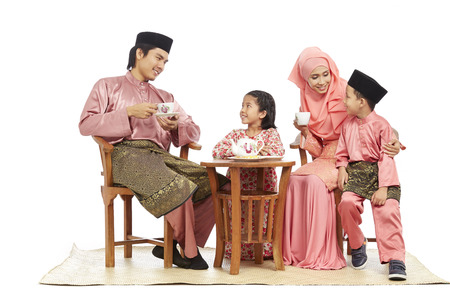 Family in traditional Malay clothes having tea together LANG_EVOIMAGES