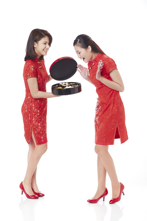 Young woman in traditional Cheongsam show an assorted tasty treats box to her friend