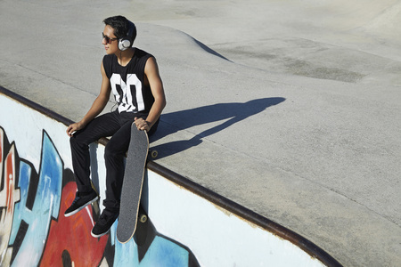 beside: Young man listening to the headphones while sitting beside a skateboard at a skate park