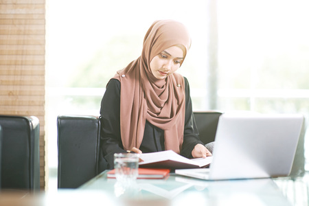 Young businesswoman reviewing documents in the office LANG_EVOIMAGES