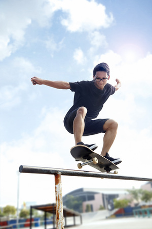 Young man skateboarding on top of railing at a skate park