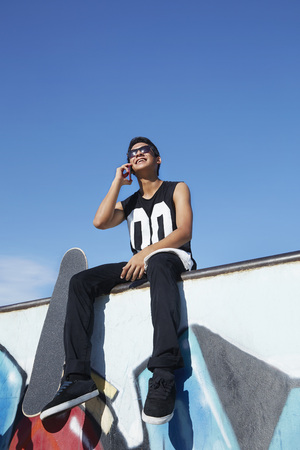 beside: Young man talking on the phone while sitting beside a skateboard at a skate park