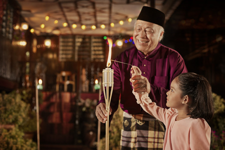 Grandfather accompany his granddaughter to play with sparklers
