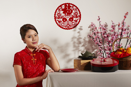 titbits: Young woman with a table full of Chinese traditional items for Chinese New Year