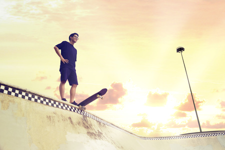 Young man looking away while standing on a skateboard at a skate park