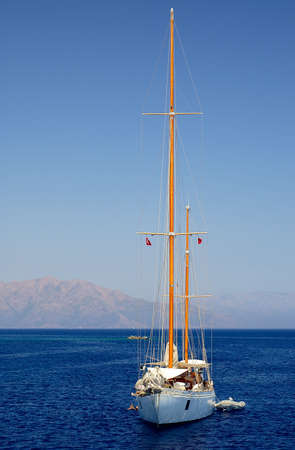 Solitary Yacht at sea with Mountains in the background photo
