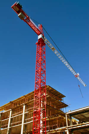 erect: Tall red crane on Construction site Stock Photo