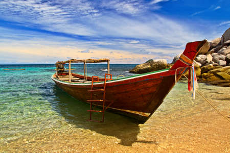 Longtail boat in tranquil bay photo