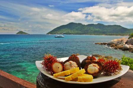 mangosteen: Plateful of exotic fruits against seaside Stock Photo