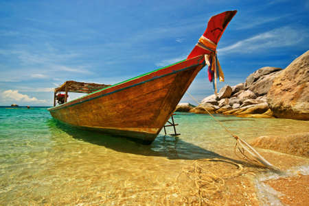 Longtail boat anchored at a beach photo