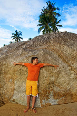 Man standing against a Huge Stone photo
