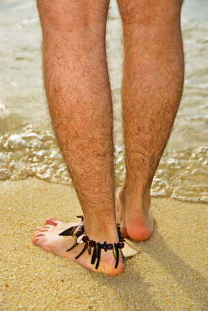 hairy closeup: mans feet stepping into the sea Stock Photo