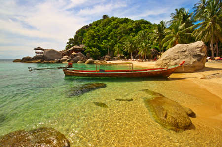 Exotic beach with long-tailed boat anchored at the shore Stock Photo - 2073740