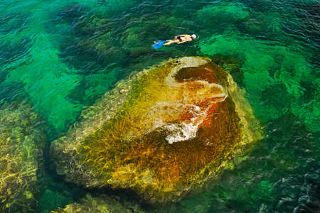 Snorkelling around a big stone in Transparent Emerald Waters photo