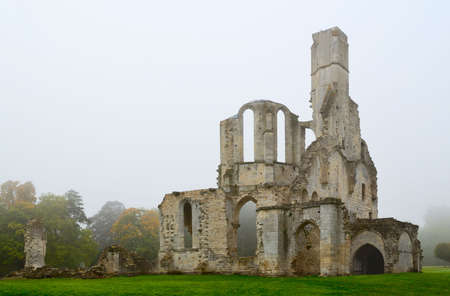 Ruined Abbey in foggy autumn morning photo