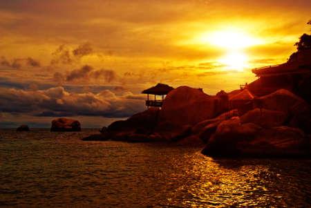 bali beach: Sunset Villa Standing in Rocks on the Sea Edge