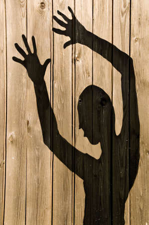 a ghost shadow or silhouette of a woman against a wooden fence photo