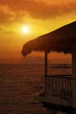 tropical sea bungalow porch  at sunset photo