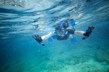 waters: man snorkeling in clear sea waters