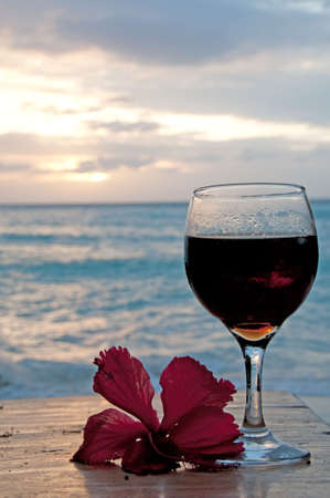 Glass of wine on the see shore with a flower photo