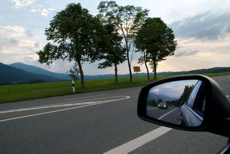 Road with a car in the sideview mirror of a  car photo