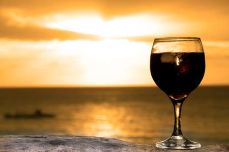 Glass of wine on the see shore in a lovely evening photo