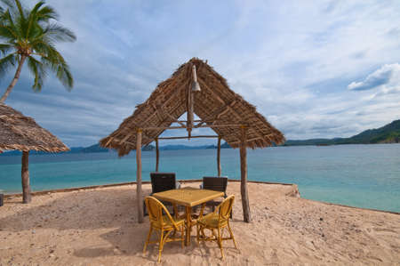Table with chairs and a tropical hut on the beach photo