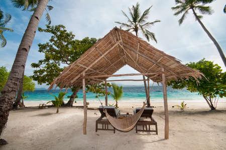 An empty hut and a hammock on a tropical beach photo