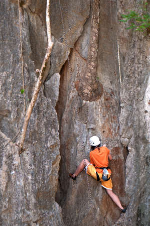 female alpinist climbing a rock photo