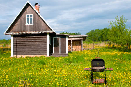 garden barbecue: Summer log house on a meadow with a BBQ in front. Stock Photo