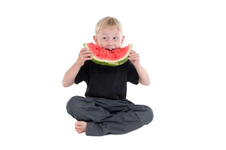 eagerly: Young Boy eating a watermelon eagerly