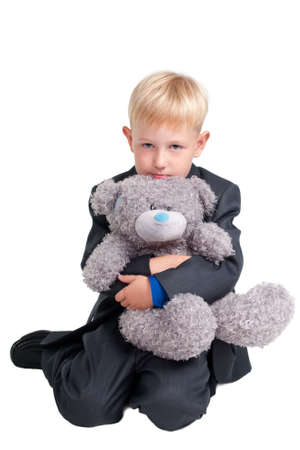 Portrait of a seroius young boy and his teddy bear photo